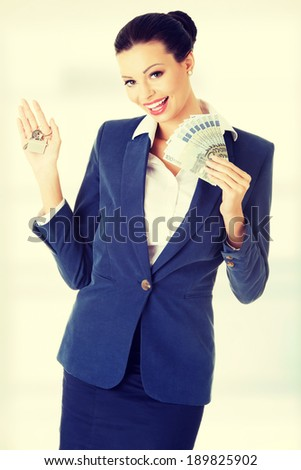 Beautiful young woman holding euro and house keys- real estate loan concept - stock photo
