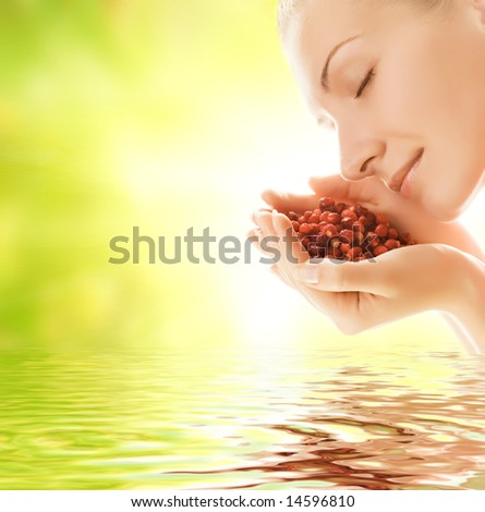 Beautiful young woman holding handful of fresh strawberries reflected in rendered water - stock photo