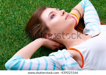 Beautiful young woman holding hands behind head and lying on the green grass - stock photo