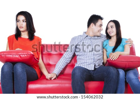 Beautiful young woman holding hands with man sitting near his girlfriend  - stock photo