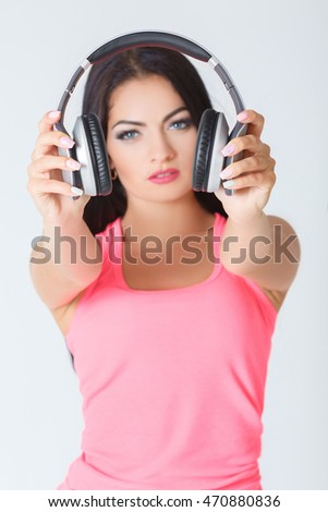 beautiful young woman holding headphones in his hand. focus on headphones