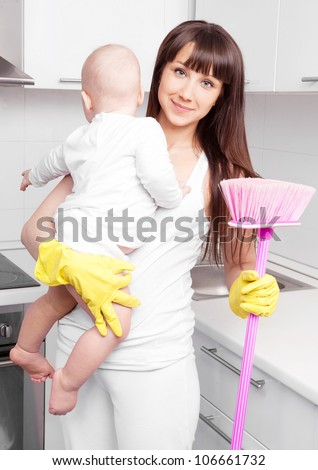 beautiful  young woman holding her baby and cleaning the furniture in the kitchen - stock photo