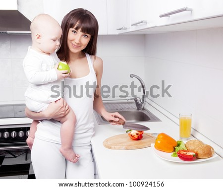 beautiful  young woman holding her baby and cutting vegetables for the salad in the kitchen