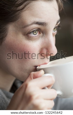 Beautiful young woman holding her morning cup of coffee. - stock photo