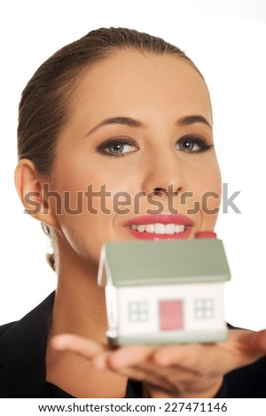 Beautiful young woman holding house model - stock photo