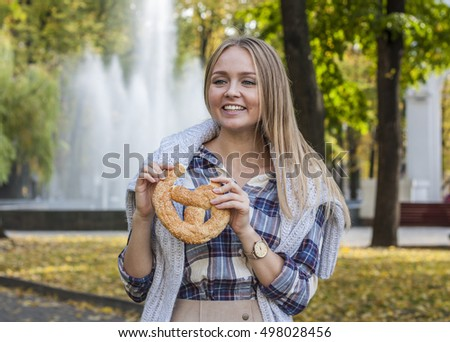 Beautiful young woman holding pretzel. Oktoberfest  in Germany