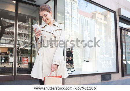Beautiful young woman holding smart phone, smiling by clothing store window display with manikins in city street, shopping bags outdoors. Female consumer using technology in exterior, lifestyle.