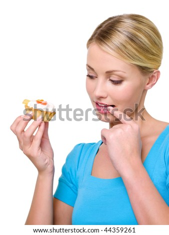 Beautiful young woman holding sweet cake and looking on it