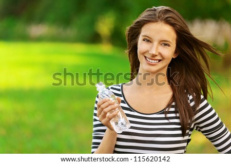Beautiful young woman holding water bottle, against green of summer park. - stock photo
