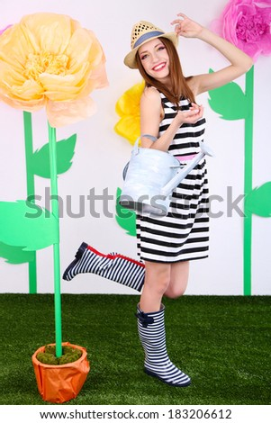 Beautiful young woman holding watering can on decorative background - stock photo