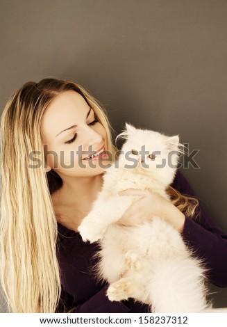 Beautiful young woman holding white Persian kitten - stock photo