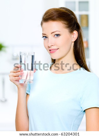 Beautiful young woman holds a glass with water on kitchen - stock photo