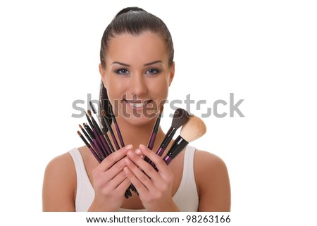Beautiful young woman holds the make-up brushes. over white background - stock photo