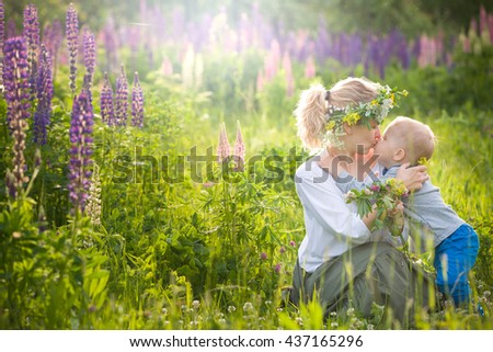 Beautiful young woman hugging and kissing her adorable little toddler boy on a sunny flower meadow. Happy family enjoying sun in the park on s summer day. Mother with child on sunset. outdoors.   - stock photo