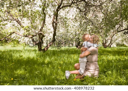 Beautiful young woman hugging her son in a blooming garden. Outdoors. Happy family walking in the park on a summer sunny day. Mother and kid boy. Apple blossom and happy family - stock photo