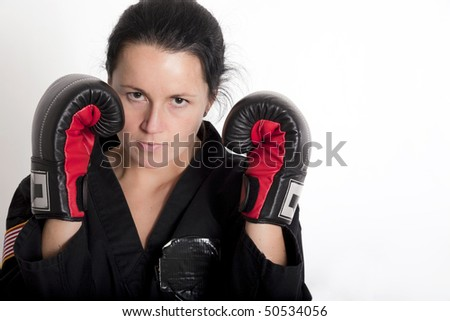 Beautiful young woman in a boxing stance wearing a black martial arts uniform and boxing style gloves. - stock photo
