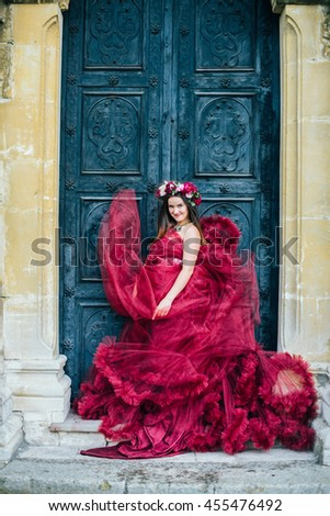 Beautiful young woman in a bright red dress and a crown of white spring flowers posing against the backdrop of the ancient door. Wind fanning,overblow, fan cloud dress. Brunet girl  with wrath.