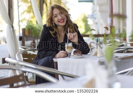 beautiful young woman in a cafe outside