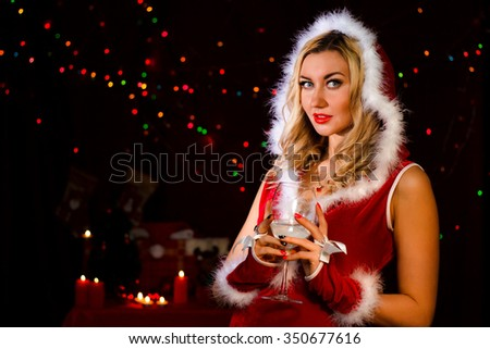 Beautiful young woman in a Christmas clothes at the background of the magic lights