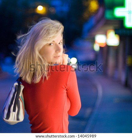 Beautiful young woman in a city at night - stock photo