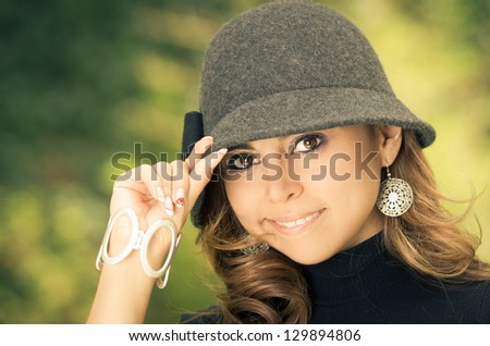 Beautiful young woman in a fashion pose with a hat - stock photo