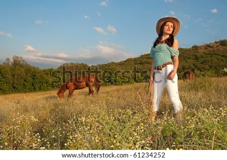 beautiful young woman in a field, the horse is grazing, open space, cowboy - stock photo