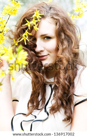 beautiful young woman in a flowering spring tree - stock photo