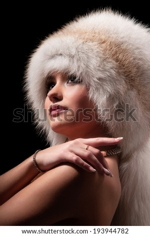 beautiful young woman in a fur hat - stock photo