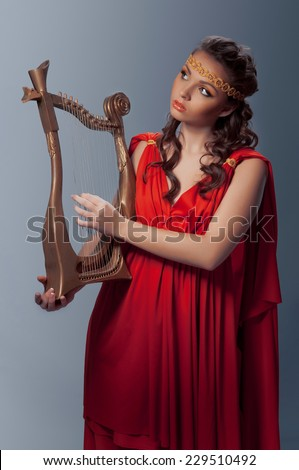 beautiful young woman in a Greek dress playing the harp - stock photo