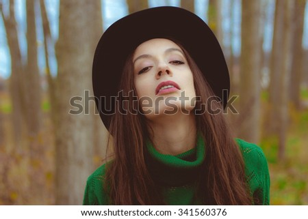 beautiful young woman in a green sweater with a hat, close up