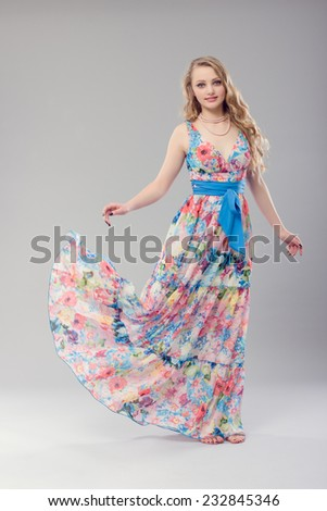 Beautiful young woman in a long dress color. - stock photo