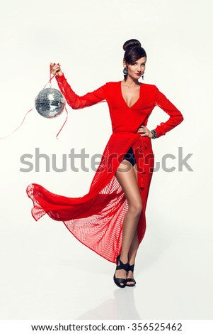 beautiful young woman in a long red dress holding a disco ball. Carnival fashion photo - stock photo