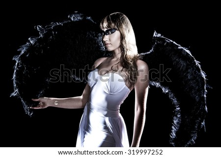 Beautiful young woman in a long white dress and with black wings isolated over black background