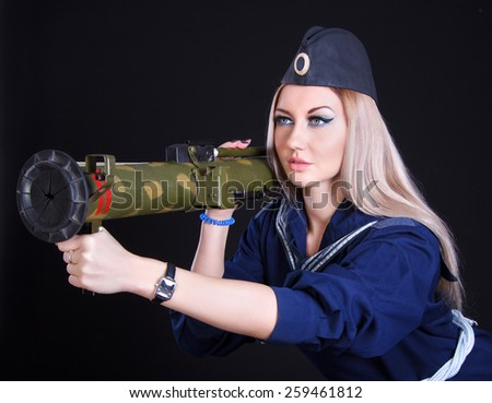 Beautiful young woman in a marine uniform with a grenade launcher over black background - stock photo