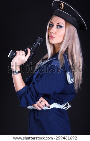 Beautiful young woman in a marine uniform with a gun over black background - stock photo