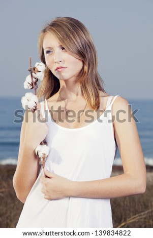 Beautiful young woman in a meadow holding and smelling a cotton plant