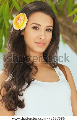 Beautiful young woman in a outdoor garden patio setting with a flower in her hair. - stock photo