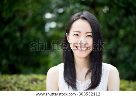 beautiful young woman in a park - stock photo