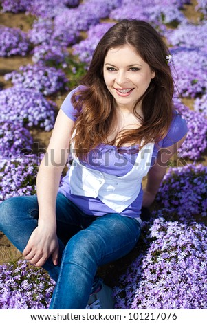 Beautiful young woman in a park on a background of bright violet flowers in spring.