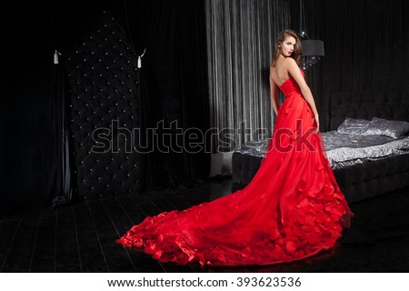 Beautiful young woman in a red dress, the background interior. Elegant young woman in dress, NEW YEAR