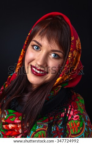 Beautiful young woman in a red traditional Russian shawl on black background