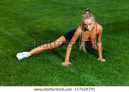 Beautiful young woman in a sports suit doing exercises on a green field stadium - stock photo