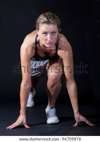 Beautiful young woman in a sprinters crouch - stock photo