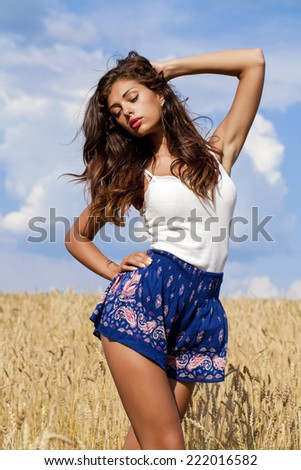 Beautiful young woman in a wheat golden field - stock photo