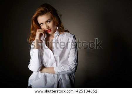 Beautiful young woman in a white man's shirt on dark background - stock photo