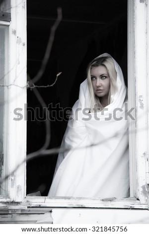 Beautiful young woman in a white sheet near the window - stock photo