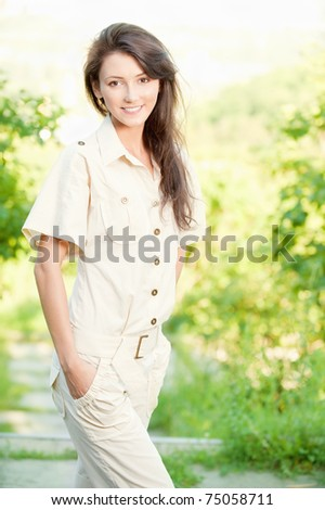 beautiful young woman in a white suit walking in the park - stock photo