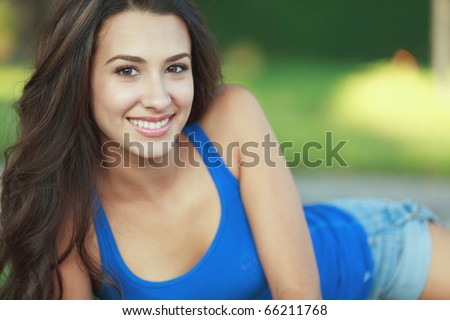 Beautiful young woman in an outdoor lifestyle pose. - stock photo