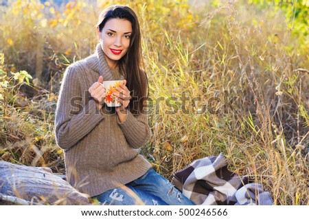 Beautiful young woman in autumn forest getting warm with cup of hot tea from thermos jug