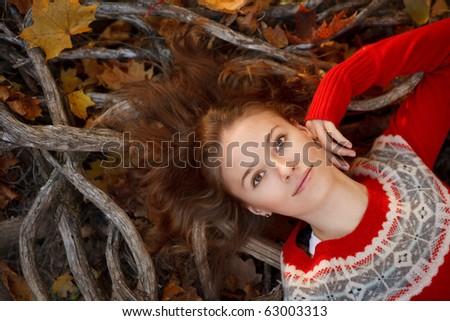 Beautiful young woman in autumn park. Top view - stock photo